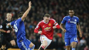 Chelsea captain John Terry tries to tackle his Manchester United counterpart Wayne Rooney